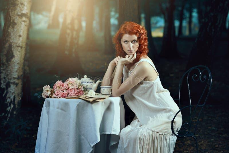 有红色头发的美丽的妇女在浪漫森林里 免版税图库摄影