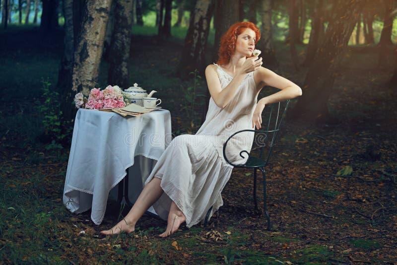 有红色头发的美丽的妇女在浪漫超现实的光 库存图片
