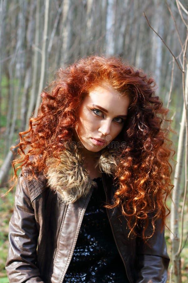 有红色头发的美丽的妇女在皮夹克在森林里摆在 免版税库存图片