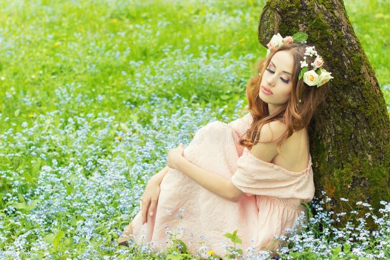 有红色头发的美丽的性感的女孩有在她的坐在一件桃红色礼服的一棵树附近的头发的花的在有蓝色花的草甸 免版税库存图片