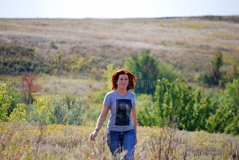 有红色头发的年轻美丽的苗条女孩连同温暖一个干草的夏天横跨领域在晴天 图库摄影