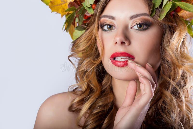 有红色头发秋天的肖象样式时尚美丽的性感的女孩与色的叶子和山脉灰颜色明亮的tre花圈  免版税图库摄影