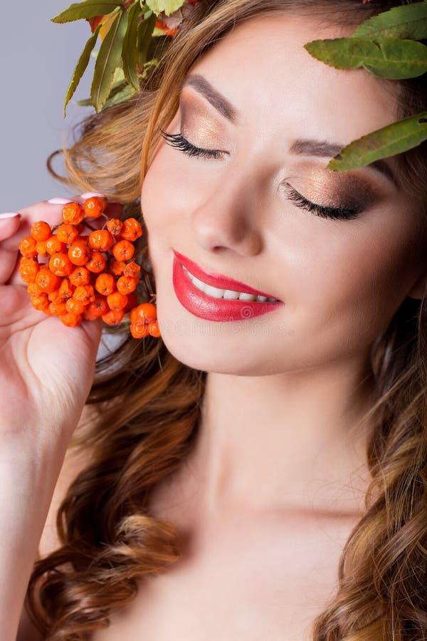 有红色头发秋天的肖象样式时尚美丽的性感的女孩与色的叶子和山脉灰颜色明亮的tre花圈  免版税库存图片