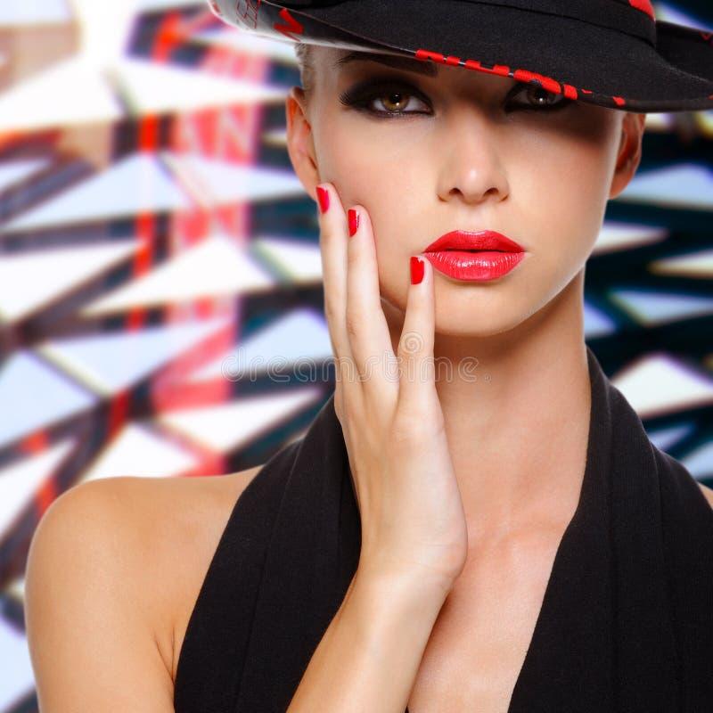 有红色嘴唇和钉子的美丽的妇女在黑帽会议 免版税库存照片