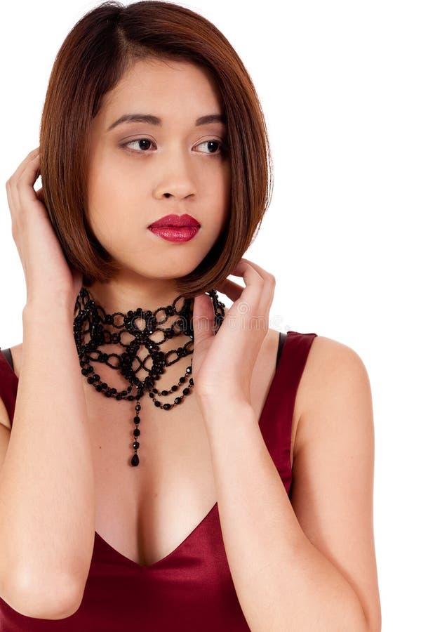 有红色嘴唇和首饰的年轻可爱的亚裔妇女  图库摄影