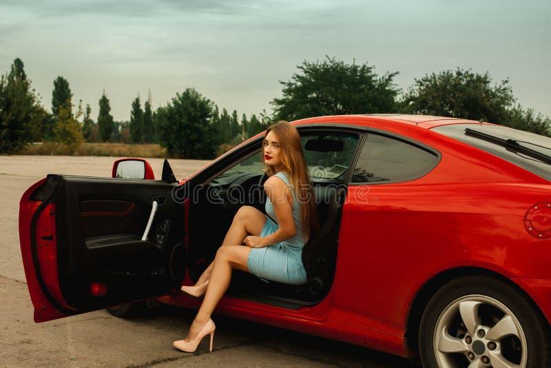 有红色嘴唇的女孩在红色汽车 免版税库存照片