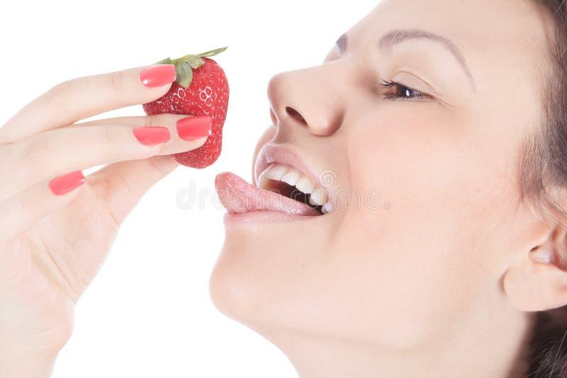 有红色嘴唇的妇女吃草莓的 免版税库存图片