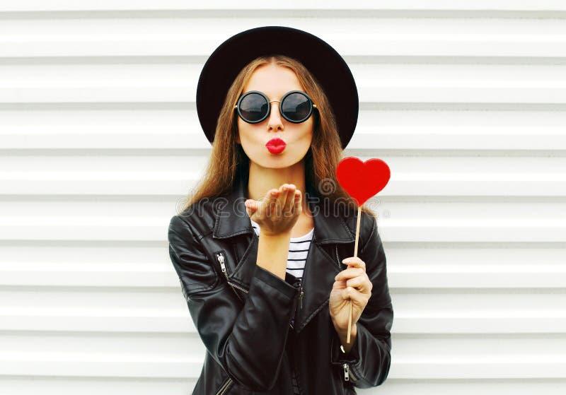 有红色嘴唇的时尚相当甜少妇送与穿在白色的棒棒糖心脏的空气亲吻黑帽会议皮夹克 库存照片