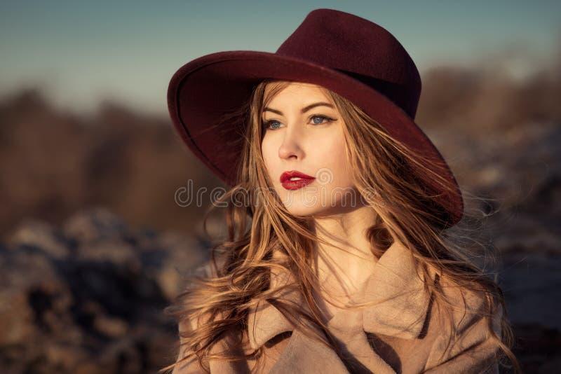 有红色嘴唇的端庄的妇女在帽子 免版税库存图片