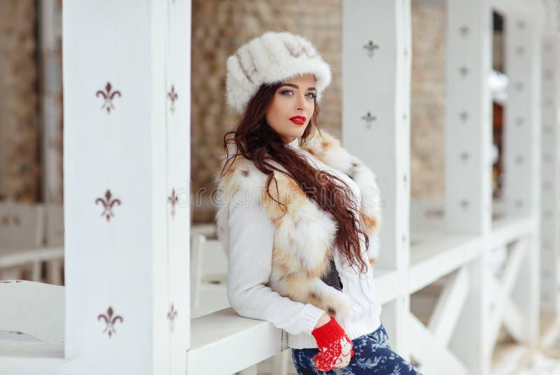 有红色嘴唇的美丽的性感的深色的女孩在毛皮背心和帽子 免版税库存照片