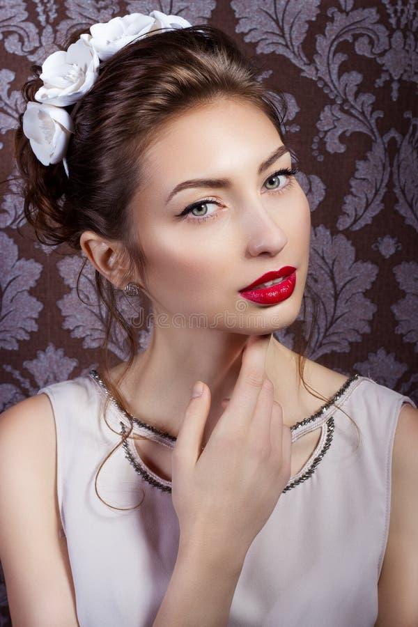有红色嘴唇的美丽的年轻性感的端庄的妇女,与白花的美好的时髦的发型在她的头发,方式 免版税库存照片