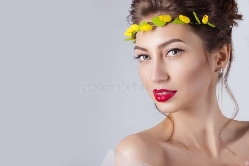 有红色嘴唇的美丽的年轻性感的端庄的妇女,有黄色玫瑰花圈的美丽的头发在头的有露出的肩膀的 免版税图库摄影