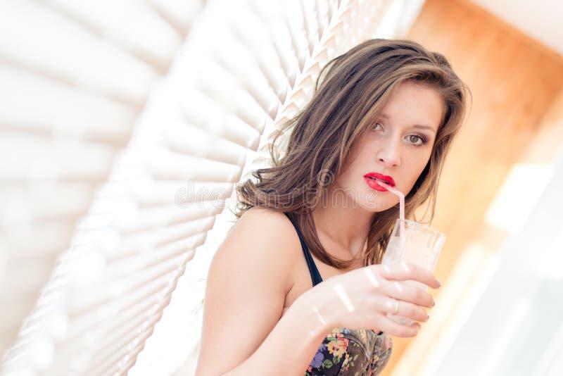 有红色嘴唇的诱人的美丽的年轻深色的妇女喝与从玻璃的秸杆的站立近的窗帘 免版税图库摄影