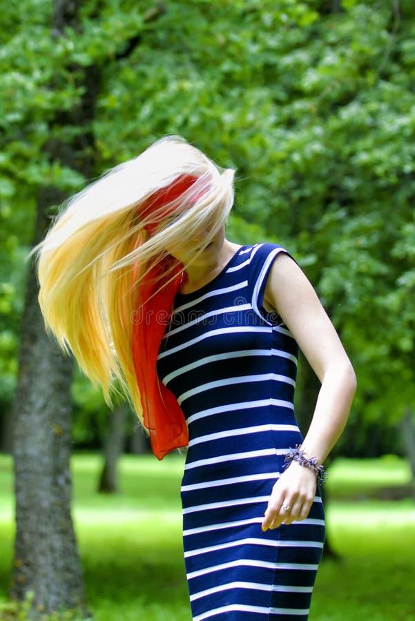 有红色围巾和镶边的礼服跳舞的白肤金发的女孩 免版税图库摄影