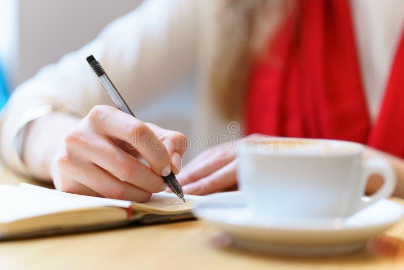 有红色围巾的欧洲妇女由笔写着某事在笔记薄在白色咖啡附近在桌 库存照片