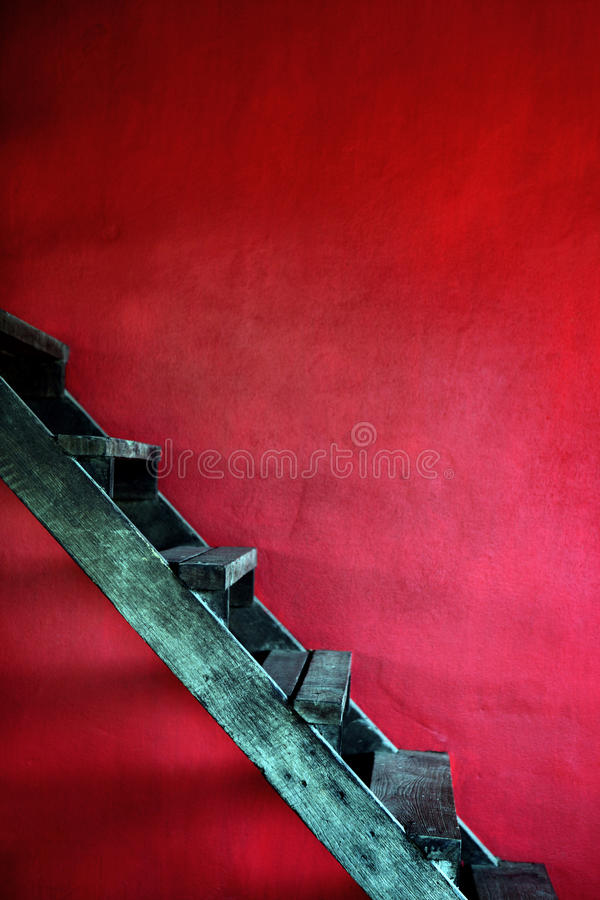 有红色水泥墙壁的葡萄酒生锈的木台阶 库存图片