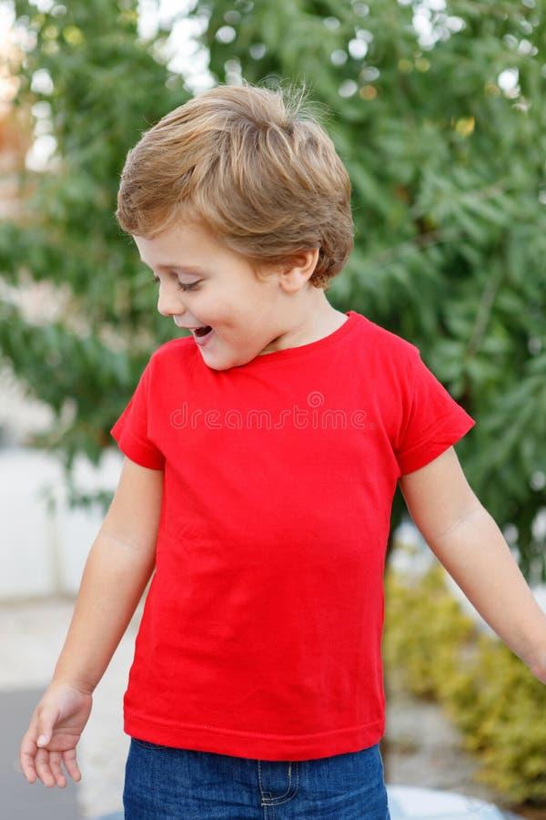 有红色T恤杉的愉快的孩子在庭院里 免版税库存照片