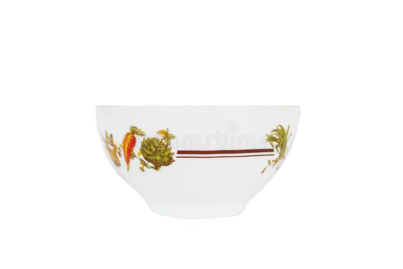 有红萝卜和植物装饰的白色瓷碗 正面图 免版税库存图片