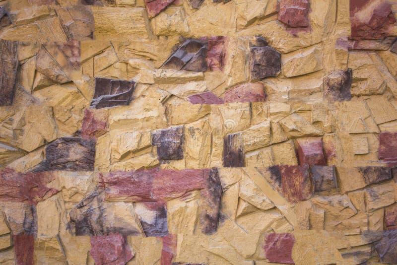 有红褐色和灰色斑点和深刻的安心的黄色石墙 毛面纹理 库存照片