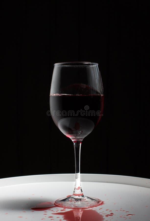 有红酒的葡萄酒杯在一张白色桌上 免版税库存图片