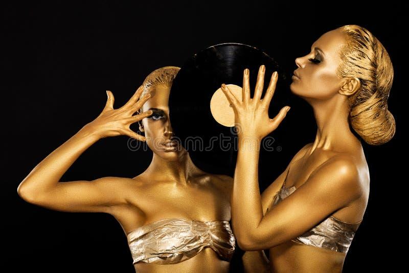 迷信。 妇女拿着减速火箭的唱片的DJs。 意想不到的金子Badyart。 表现 免版税库存照片