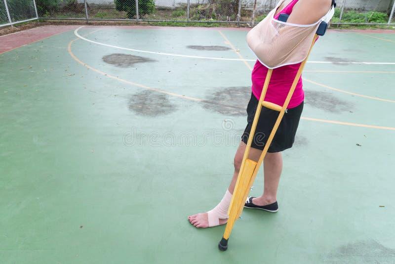 有纱绷带、胳膊吊索和木拐杖的受伤的妇女佩带的运动服痛苦的胳膊在绿色地板上 免版税库存照片