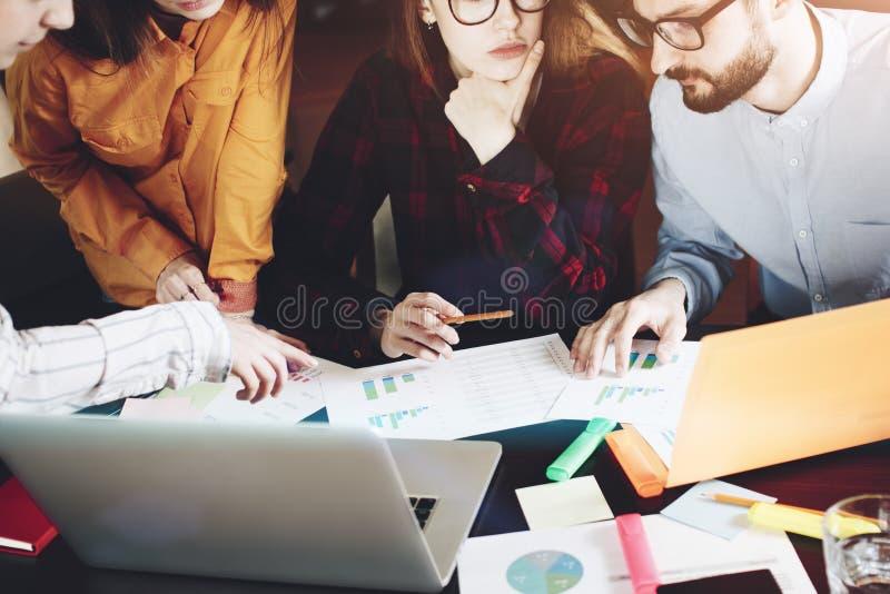 有纸、小配件和笔记本的人的手在讨论时 库存图片