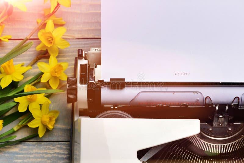 有纸和春天开花的水仙的老葡萄酒打字机开花 库存图片