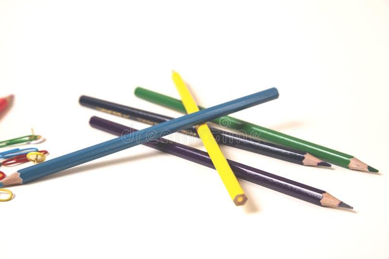 有纸夹的五颜六色的铅笔在白色书桌上 免版税图库摄影