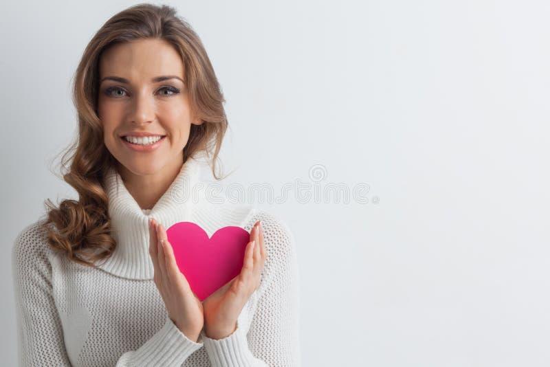 有纸心脏的微笑的妇女 免版税库存图片