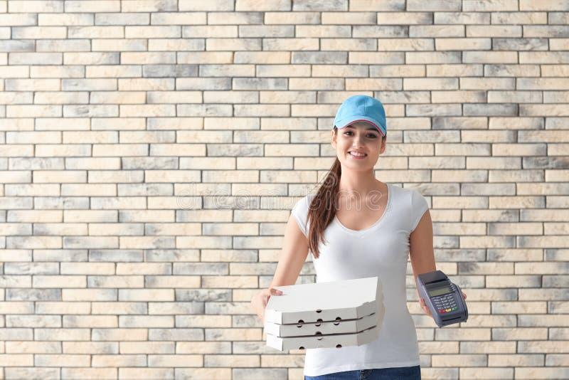 有纸板比萨箱子和付款终端的交付妇女砖墙背景的 免版税图库摄影