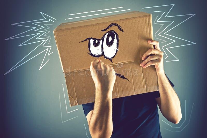 有纸板箱的人在恼怒的f他的头和乱画图画  免版税库存图片