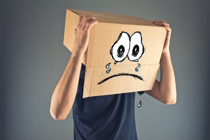 有纸板箱的人在他的头和哀伤的面孔表示 免版税图库摄影