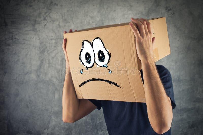 有纸板箱的人在他的头和哀伤的面孔表示 库存图片