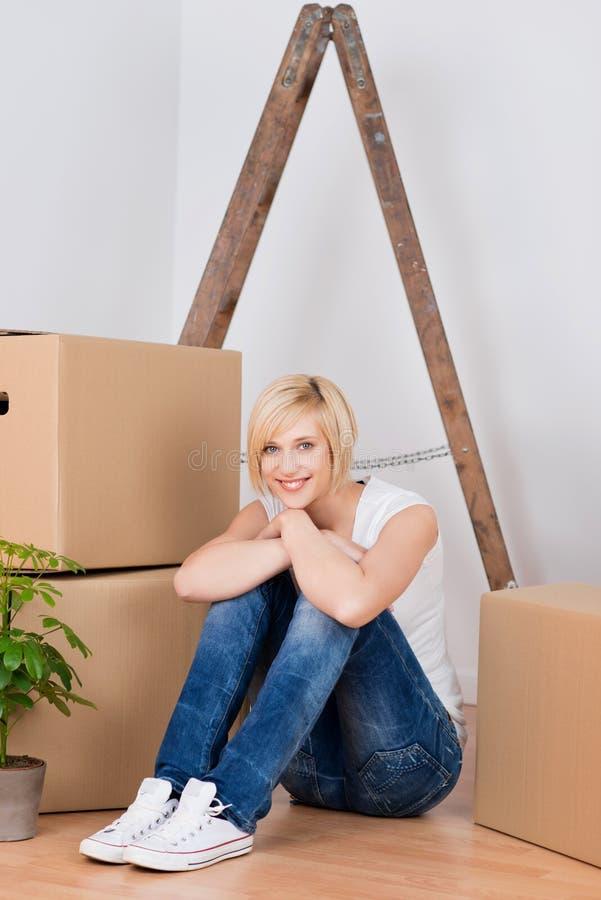 有纸板箱的少妇坐硬木地板 免版税库存照片