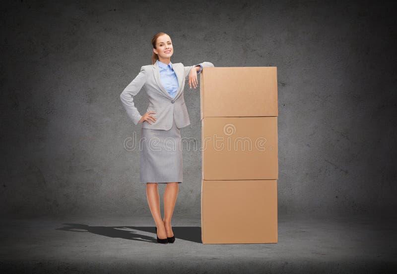 有纸板箱的微笑的女实业家 免版税库存图片