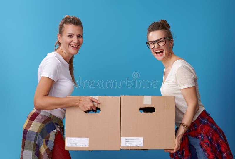 有纸板箱的微笑的现代女性室友在蓝色 免版税库存照片