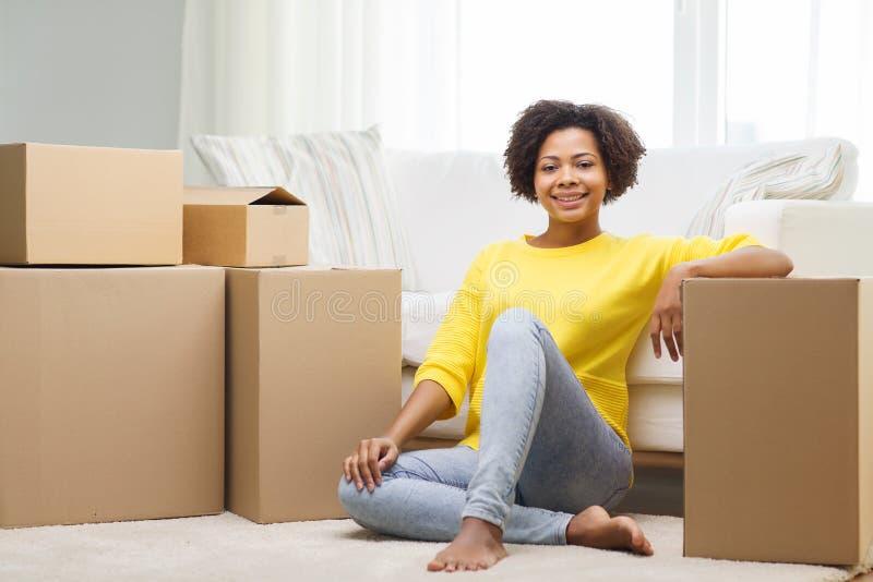 有纸板箱的愉快的非洲妇女在家 免版税图库摄影