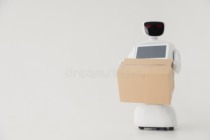 有纸板箱的有人的特点的自治机器人在手中在白色背景 机器人交付小包 发运 免版税库存图片