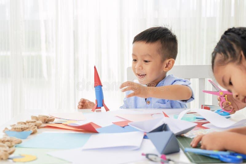 有纸火箭的可爱的男孩 免版税库存照片