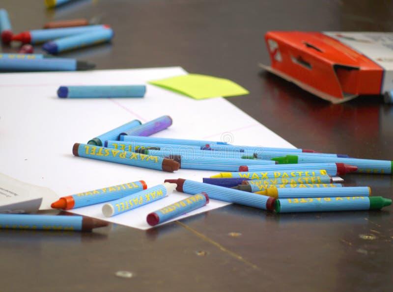 有纸的各种各样的颜色蜡笔在书桌 免版税库存照片