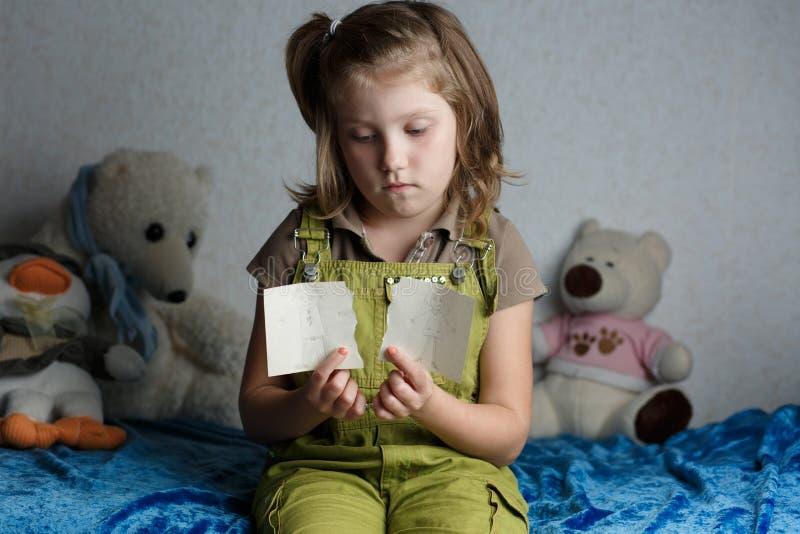 有纸的孩子在他的手离开,绘由父母,被分开 免版税库存照片