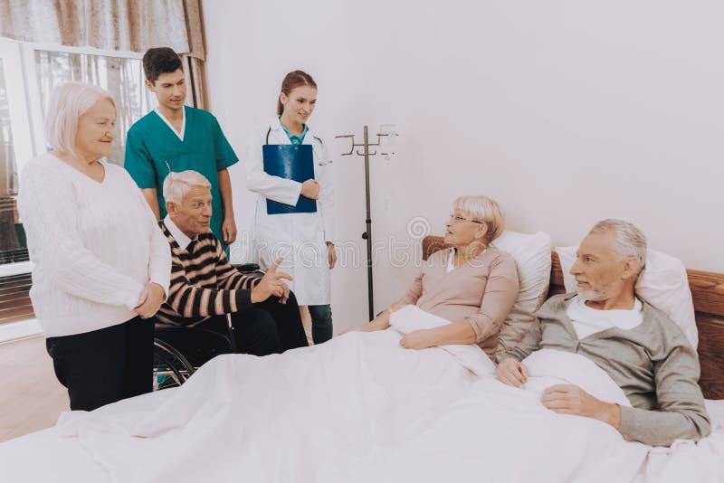 有纸的护士 客人参观年长夫妇 图库摄影