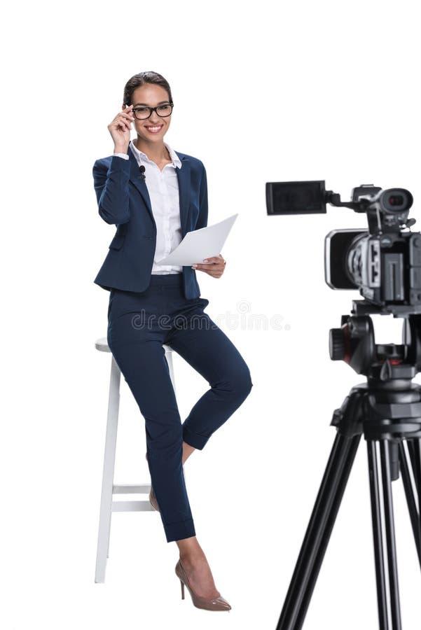 有纸的美丽的微笑的女性新闻广播员微笑和坐在照相机前面的, 图库摄影
