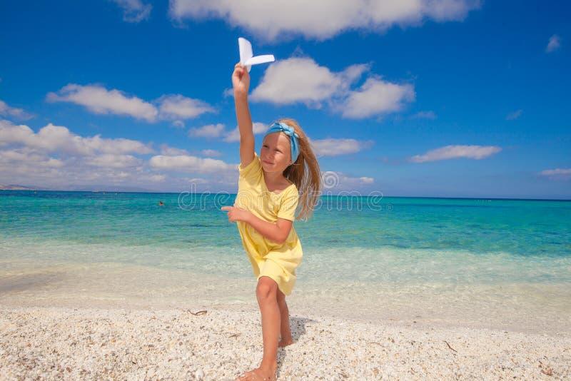 有纸飞机的愉快的小女孩在海滩期间 图库摄影
