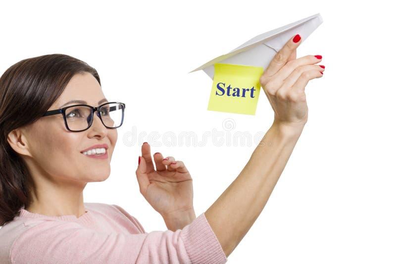 有纸飞机的愉快的成熟妇女有文本开始的,女性做一个开始,被隔绝的白色背景 免版税库存照片