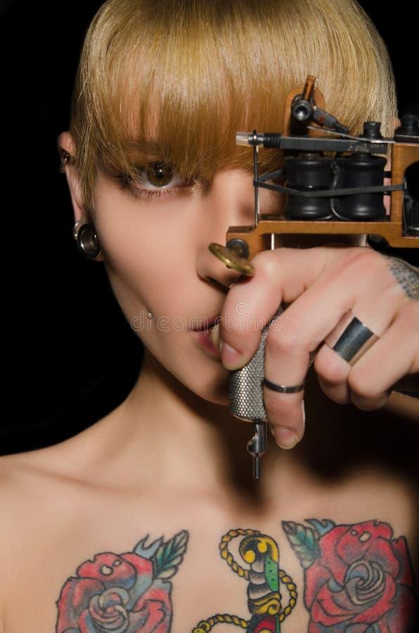 有纹身花刺机器的被刺字的美丽的妇女 免版税库存图片