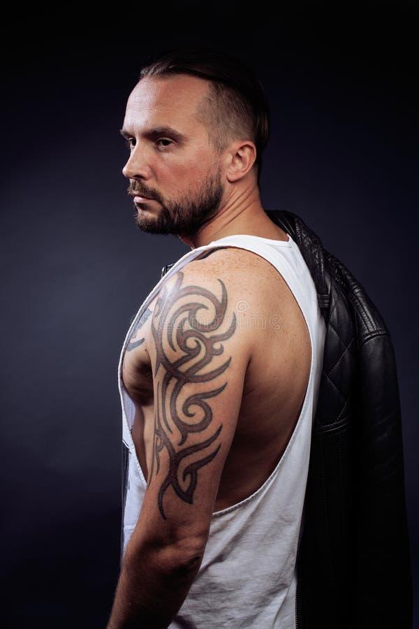 有纹身花刺的一个人在他的胳膊 强健的身体剪影  有现代理发的白种人残酷行家人,看 免版税库存照片