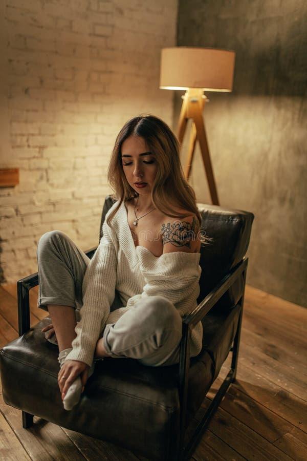 有纹身花刺的一年轻女人在她的肩膀在retr坐 免版税库存照片