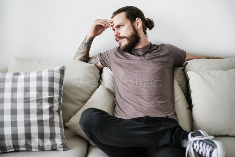 有纹身花刺的人坐长沙发 库存照片